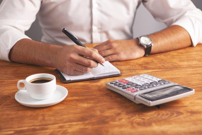 Cuaderno de la calculadora del café del hombre de negocios imagen de archivo libre de regalías