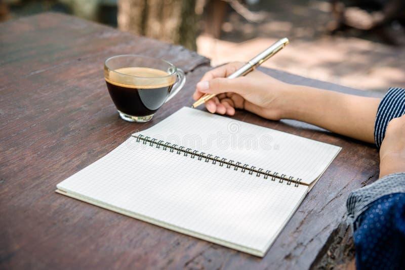 Cuaderno de la escritura de la mano de la mujer imagen de archivo libre de regalías