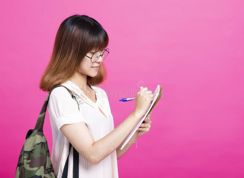 Cuaderno de la escritura del estudiante de la chica joven imagen de archivo