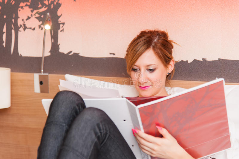 Cuaderno de la lectura de la muchacha en cama fotografía de archivo libre de regalías