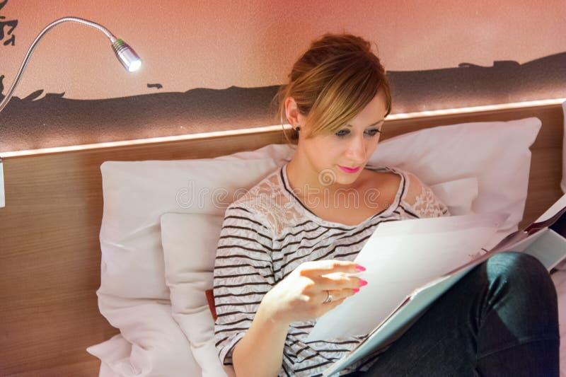 Cuaderno de la lectura de la muchacha en cama imagen de archivo