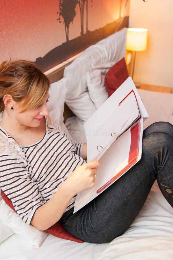 Cuaderno de la lectura de la muchacha en cama fotos de archivo