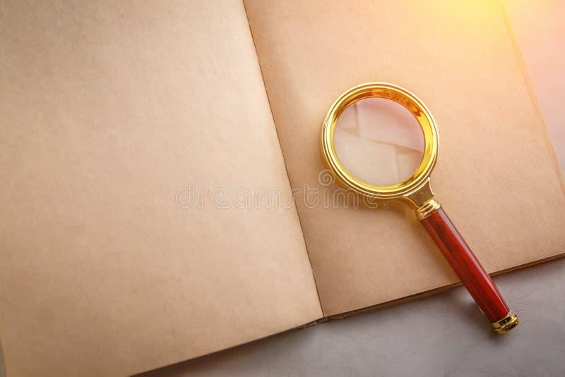 Cuaderno de la página en blanco con una lupa fotografía de archivo