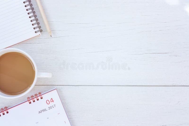 Cuaderno de la visión superior, calendario y taza de café en el tabl de madera blanco imagen de archivo libre de regalías