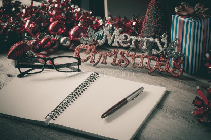 Cuaderno de notas con el lápiz en el saludo de madera de la feliz Navidad del concepto de los accesorios de escritorio a través d fotografía de archivo