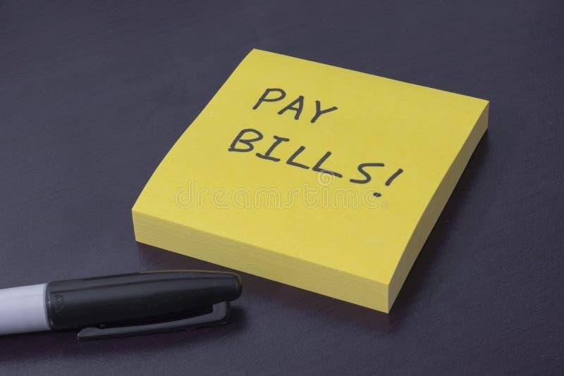 Cuaderno de notas pegajoso con el recordatorio a los proyectos ley de remuneración imagen de archivo libre de regalías