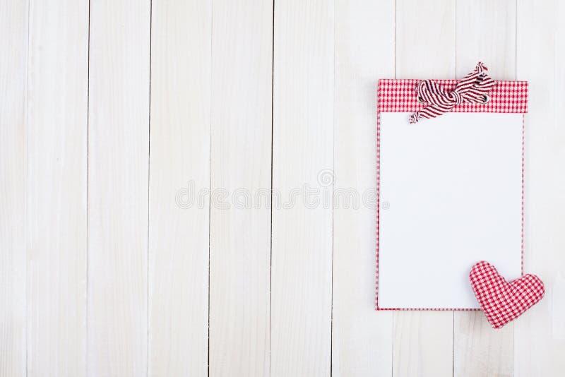 Cuaderno de notas rojo de la tela escocesa en la cerca blanca fotos de archivo libres de regalías