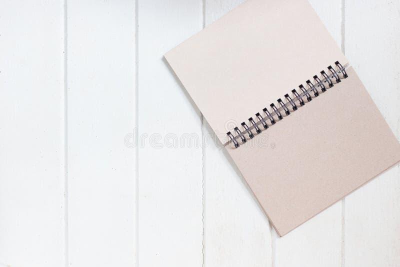 Cuaderno de papel en blanco en el tablero de madera blanco foto de archivo