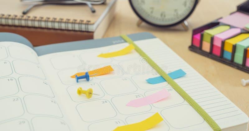 Cuaderno del diario del horario en la tabla la gestión recuerda resolver concepto imagen de archivo