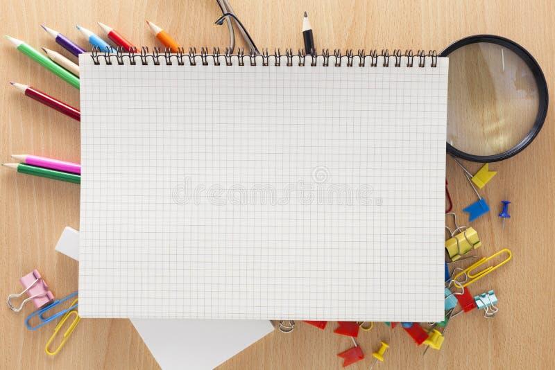 Cuaderno del Libro Blanco con los materiales de oficina en fondo de madera imagenes de archivo