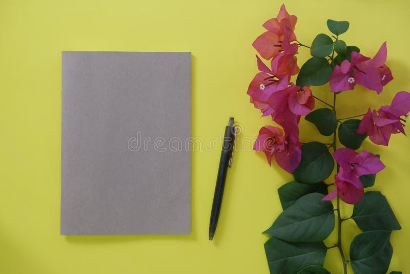 Cuaderno del marrón de la maqueta con el espacio para el texto en fondo y flores amarillos imágenes de archivo libres de regalías