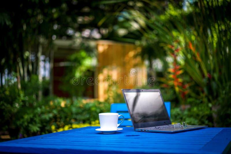 Cuaderno del ordenador/ordenador portátil, vidrios con la taza del café con leche en la tabla azul marino en el tiempo de relajac fotos de archivo
