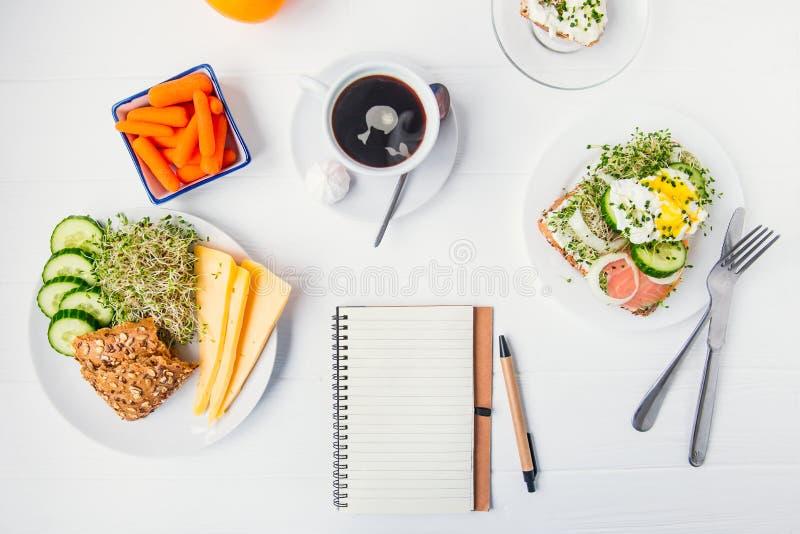 Cuaderno del planeamiento de la visión superior con el espacio de la copia y bocadillo sano del desayuno con el huevo Benedicto y imagenes de archivo