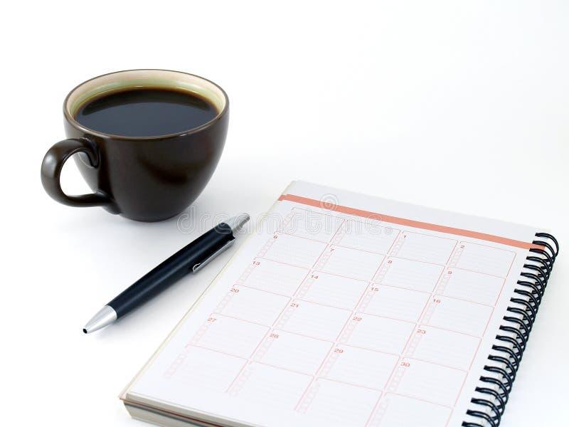 Cuaderno del primer, pluma negra y café caliente en la taza de cerámica del marrón oscuro aislada en el fondo blanco imágenes de archivo libres de regalías