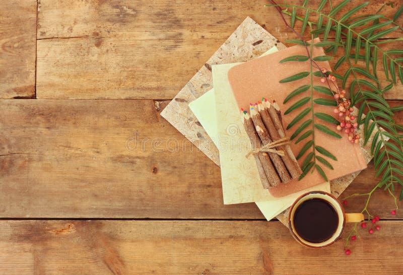 Cuaderno del vintage, papel viejo y pegado del lápiz de madera colorido al lado de la taza de café sobre la tabla de madera alist foto de archivo