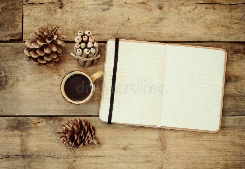 Cuaderno del vintage, papel viejo y pila de lápiz de madera colorido al lado de la taza de café sobre la tabla de madera aliste p imagen de archivo libre de regalías