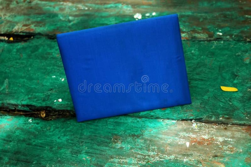 Cuaderno duro azul marino de la cubierta en la tabla vieja de madera verde foto de archivo