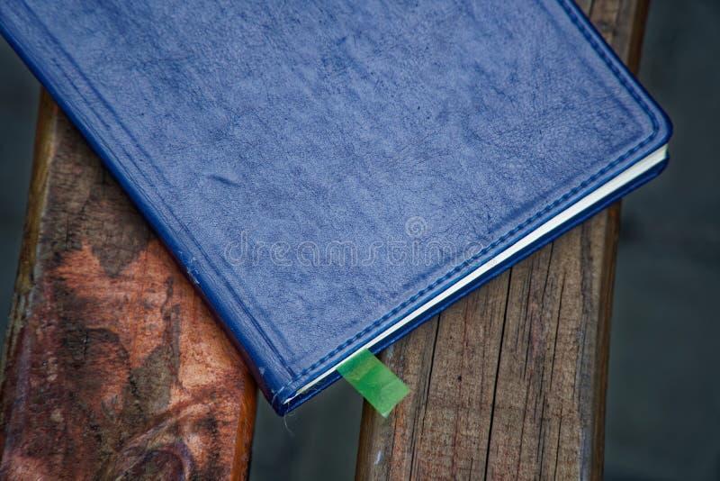 Cuaderno en banco en el parque, concepto del negocio imagenes de archivo