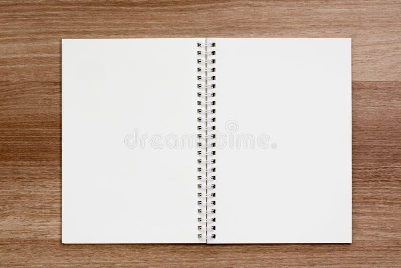 Cuaderno en blanco abierto del atascamiento espiral del anillo en superficie de madera foto de archivo