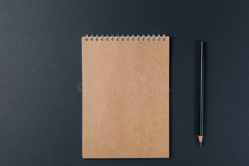 Cuaderno en blanco con el lápiz en fondo negro workplace Copie el espacio Concepto m?nimo imagen de archivo