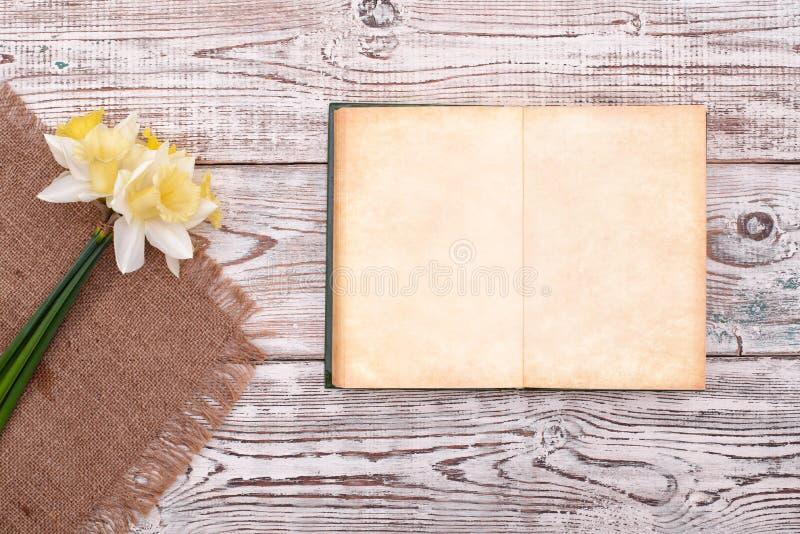 Cuaderno en blanco con la flor en la opinión superior del fondo de madera de la tabla del vintage fotografía de archivo libre de regalías