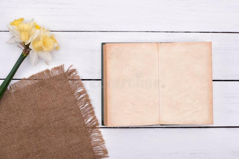 Cuaderno en blanco con la flor en la opinión superior del fondo de madera de la tabla del vintage fotos de archivo libres de regalías