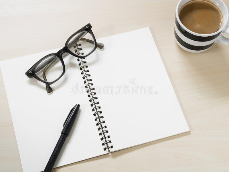 Cuaderno en blanco con las lentes, la pluma y la taza del vintage de café caliente en la tabla de madera imagen de archivo