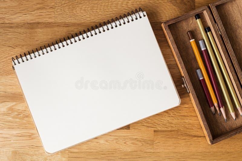 Cuaderno en blanco con los lápices en el escritorio overhead imagen de archivo