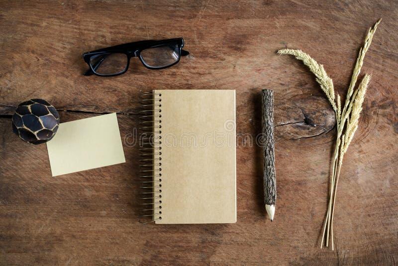 Cuaderno en blanco con los vidrios del ojo en el escritorio de madera viejo imagen de archivo libre de regalías