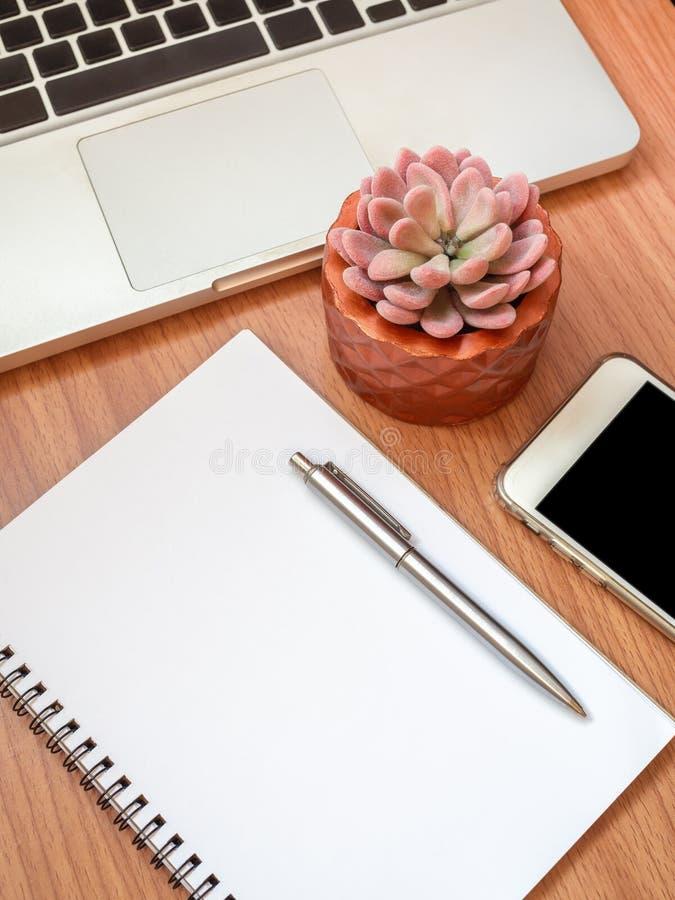 Cuaderno en blanco con smartphone, el ordenador portátil y la planta suculenta en el pote de cobre en fondo de madera de la tabla imagen de archivo