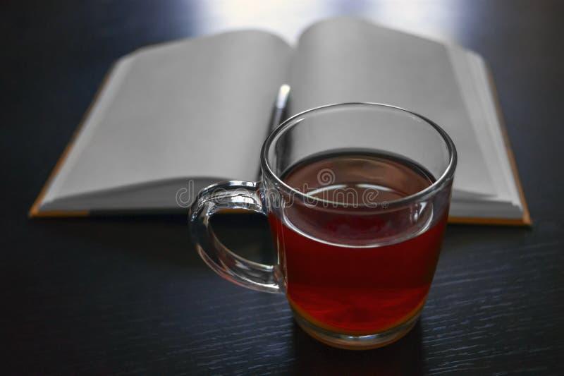 Cuaderno en blanco, pluma negra, taza de té en una tabla de madera Resoluciones del ` s del Año Nuevo Fijando las metas, consigui fotografía de archivo