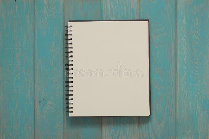 Cuaderno en el escritorio de madera azul foto de archivo