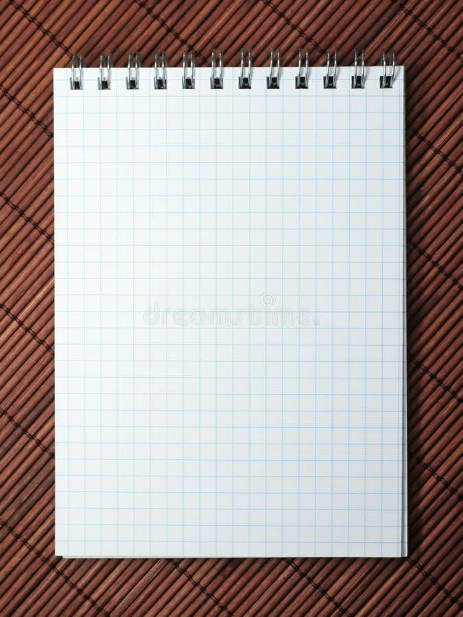 Cuaderno en la estera imagen de archivo libre de regalías
