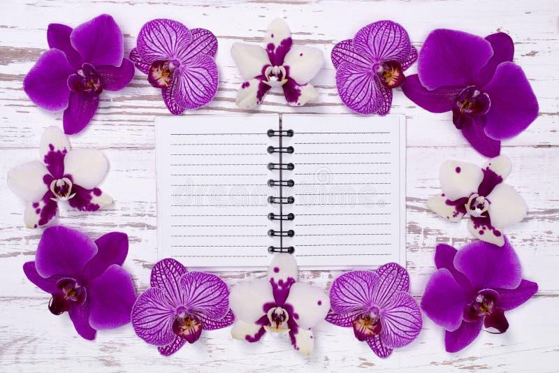 Cuaderno en la tabla de madera vieja adornada con las flores fotografía de archivo