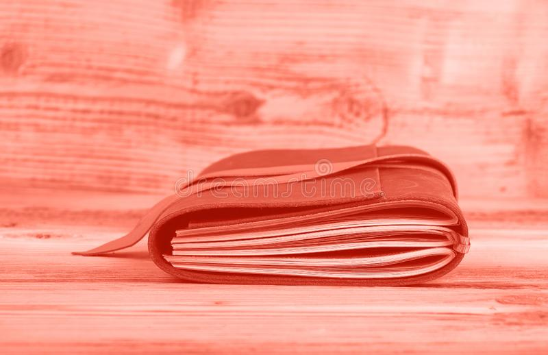 Cuaderno entonado rosado en la cubierta de cuero en la tabla fotos de archivo