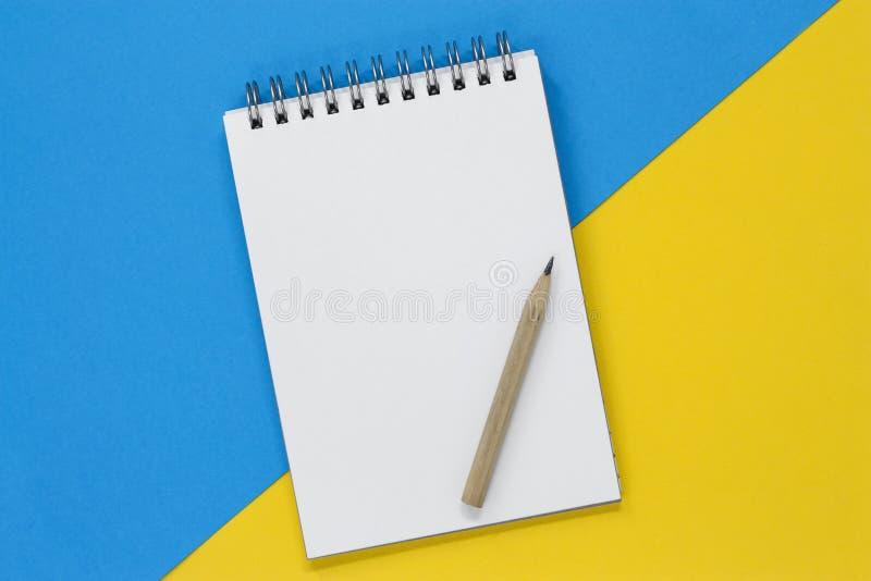 Cuaderno espiral abierto con una página en blanco y un lápiz en un fondo azul y amarillo, con el espacio de la copia foto de archivo libre de regalías