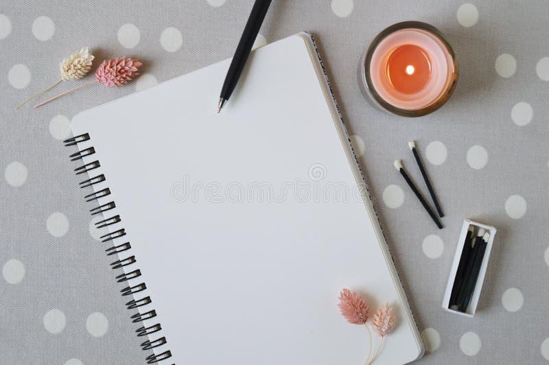 Cuaderno espiral con la p?gina vac?a, la vela coralina, las flores secadas y los partidos negros fotos de archivo