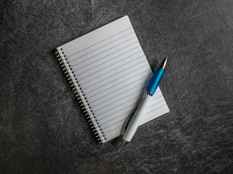 Cuaderno espiral con la página vacía y pluma en un espacio oscuro de la copia del fondo de la pizarra imagenes de archivo