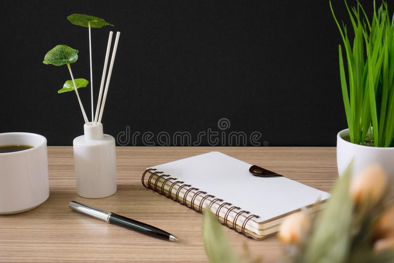 Cuaderno espiral con la taza de café y la planta en conserva en el escritorio de madera fotografía de archivo libre de regalías
