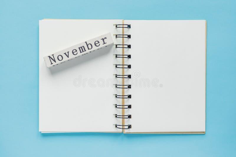 Cuaderno espiral limpio para las notas y los mensajes y barra de madera del calendario de noviembre en fondo azul Endecha plana d fotografía de archivo