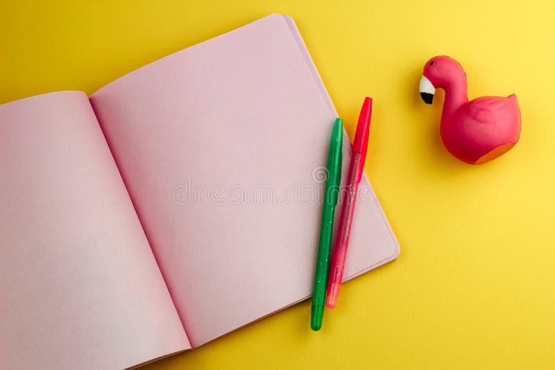 cuaderno, lápices y adorables borradores de flamingo sobre fondo amarillo, de vuelta a la escuela se burlan fotografía de archivo
