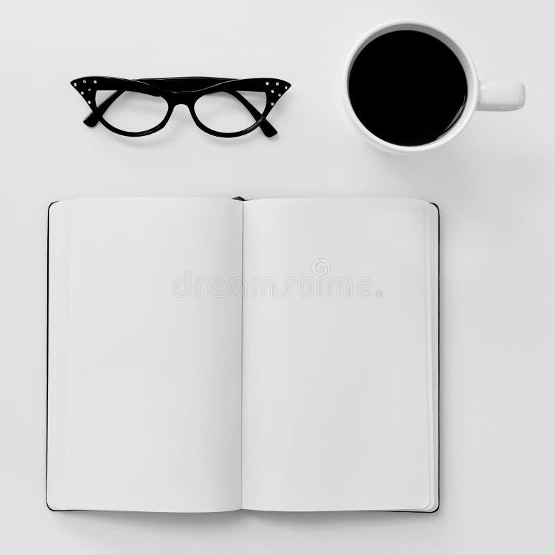 Cuaderno, lentes y taza de café en blanco en una tabla blanca foto de archivo
