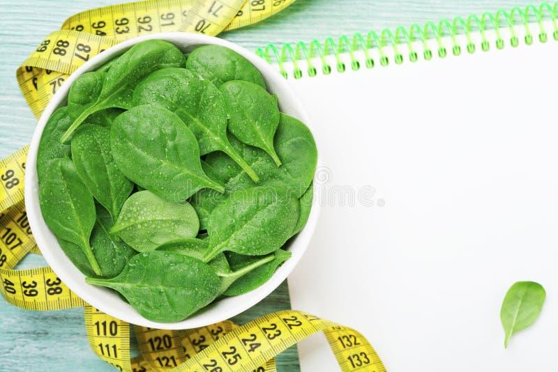 Cuaderno limpio, hojas verdes de la espinaca y cinta métrica en la tabla de madera desde arriba Dieta y concepto sano de la comid imagen de archivo
