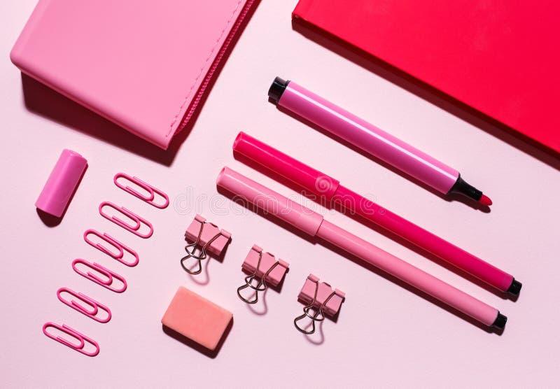 Cuaderno, mentira de la caja de lápiz en el fondo rosado fotos de archivo