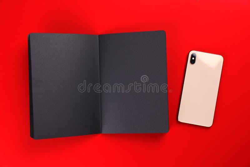 Cuaderno negro abierto con smartphone en fondo colorido imágenes de archivo libres de regalías