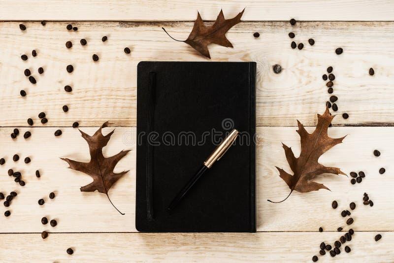 Cuaderno negro con una pluma, tres hojas caidas y granos de café imagenes de archivo