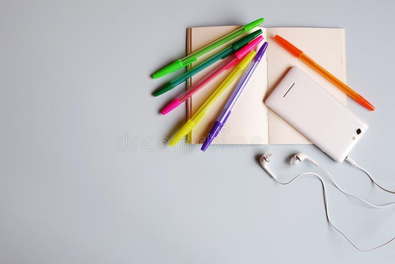 Cuaderno o diario en blanco, teléfono elegante con los auriculares y plumas multicoloras imagen de archivo libre de regalías