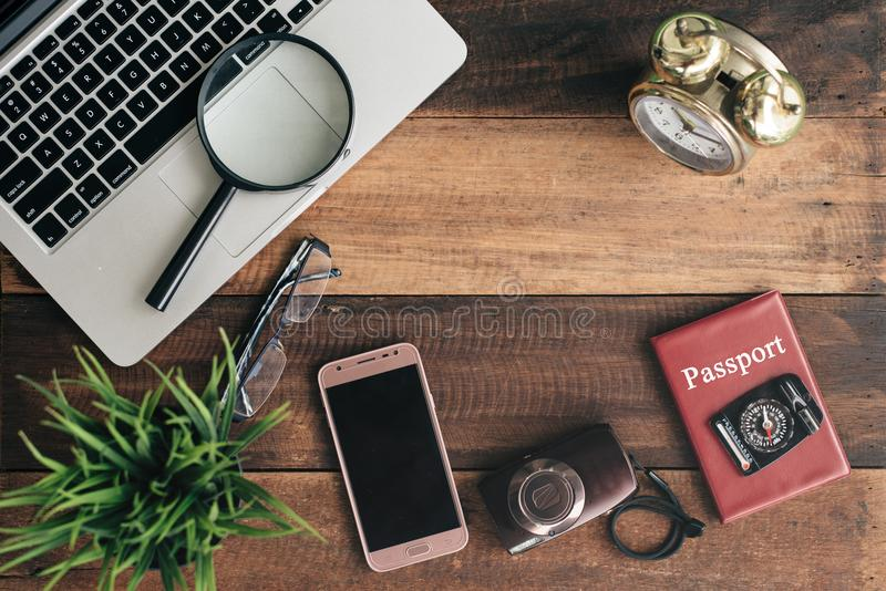 Cuaderno, ordenador portátil, smartphone, compás, pasaporte, reloj y cámara en fondo de madera de la tabla fotografía de archivo libre de regalías