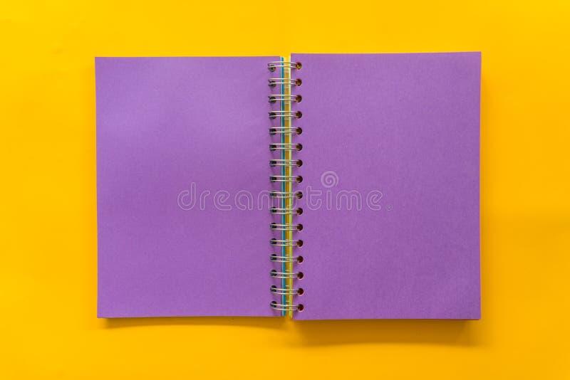 Cuaderno p?rpura en fondo amarillo fotos de archivo libres de regalías