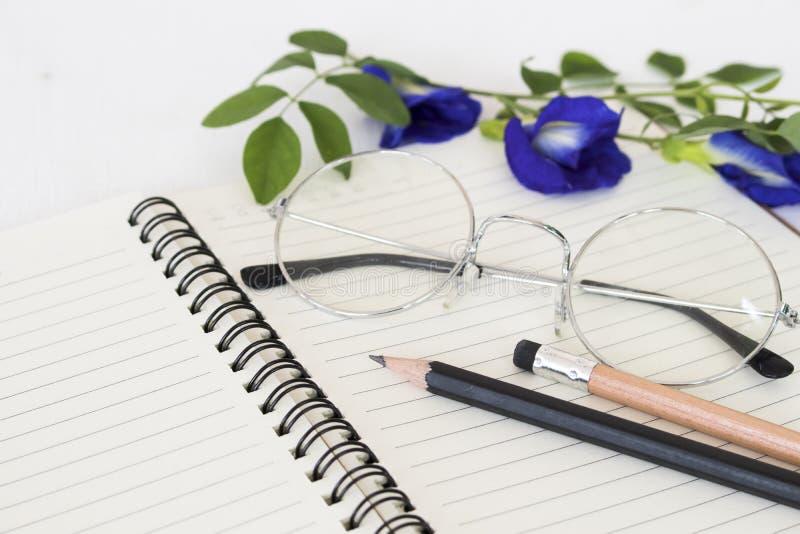 Cuaderno para el memorándum con el lápiz, gafas imagen de archivo